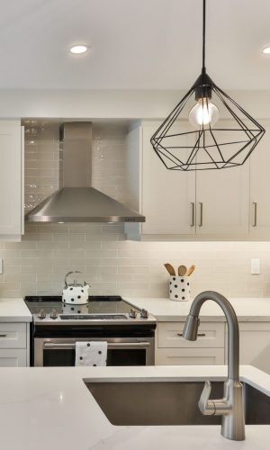 kitchen with white stone countertops with under mount sink white cabinet black accent and polkadot accessories