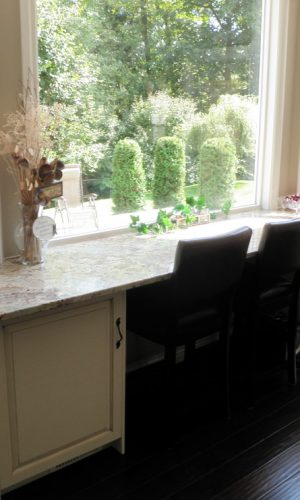 Pentagon stone countertop on white cabinet in front of window side view
